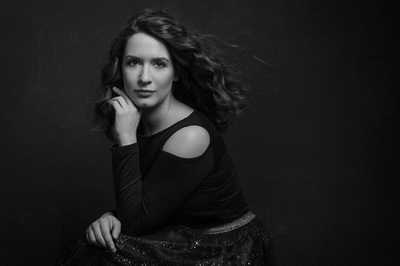 Fotografo di ritratto Ferrara - The image of a woman wearing a black dress against black backdrop using one studio light set-up