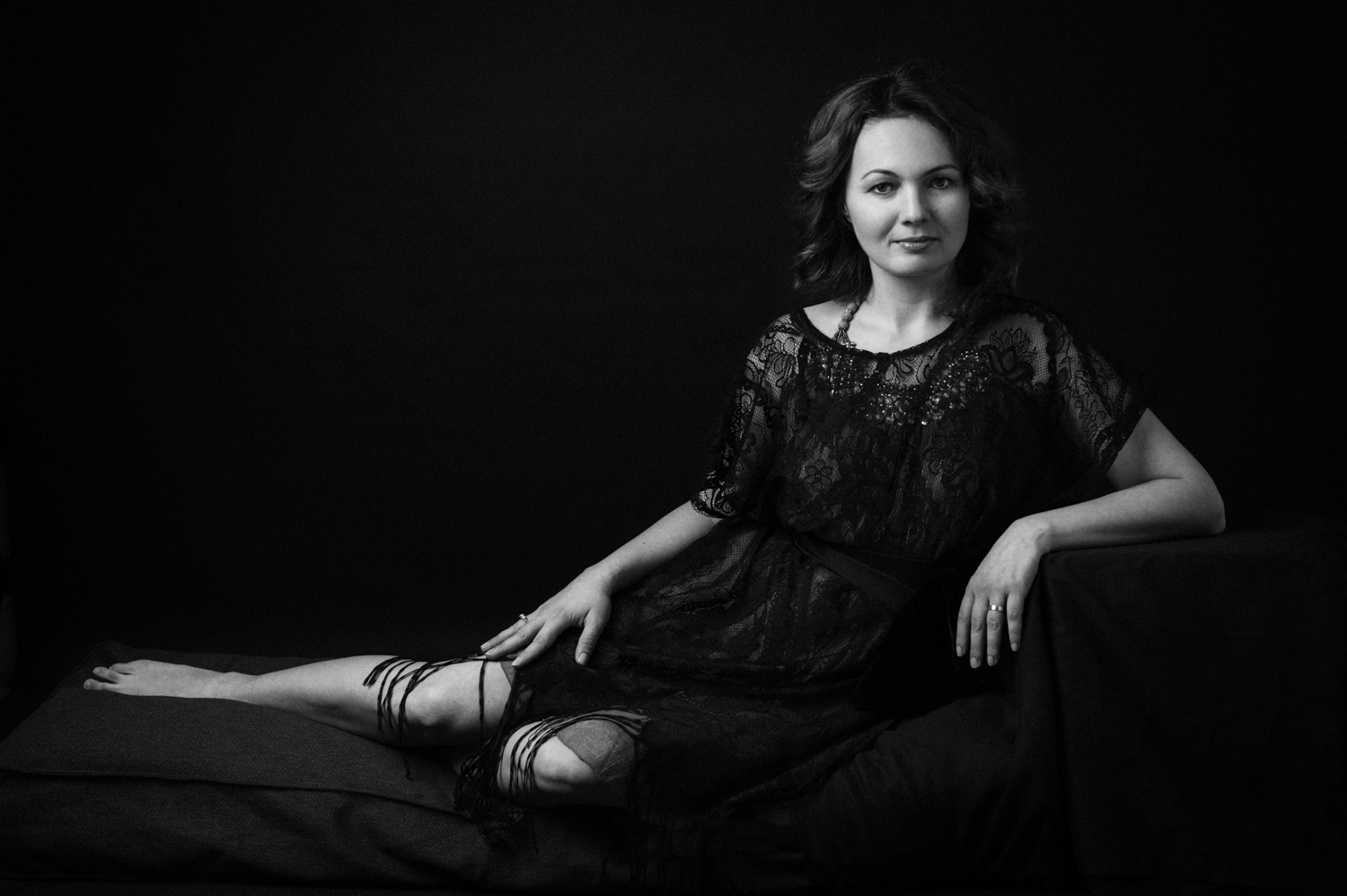 Black and white contemporary portrait of a woman wearing a black dress on a black backrgound